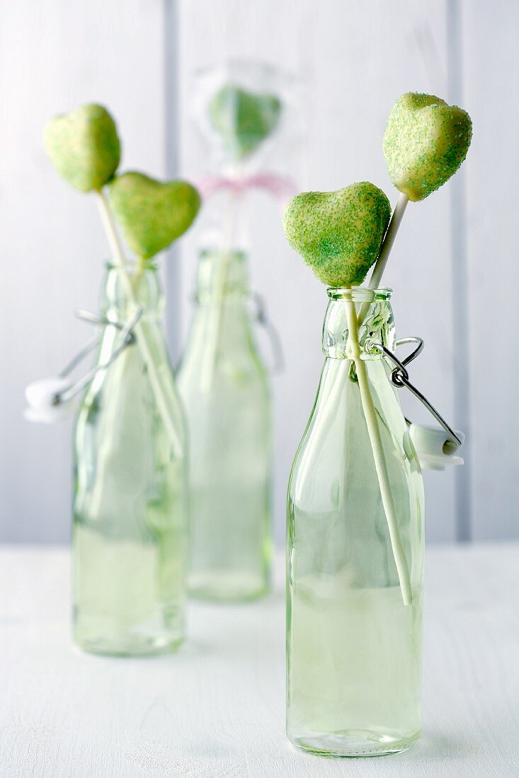 Green heart-shaped cake pops in light green bottles