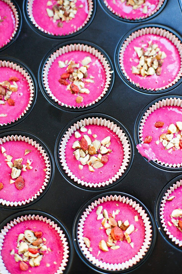 Unbaked red nut muffins in a muffin tin