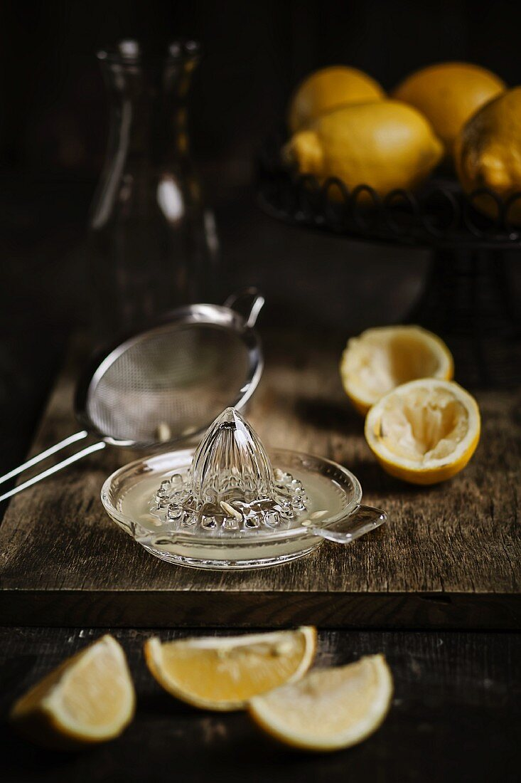 Lemon juice in a lemon press with a bowl of lemons in the background