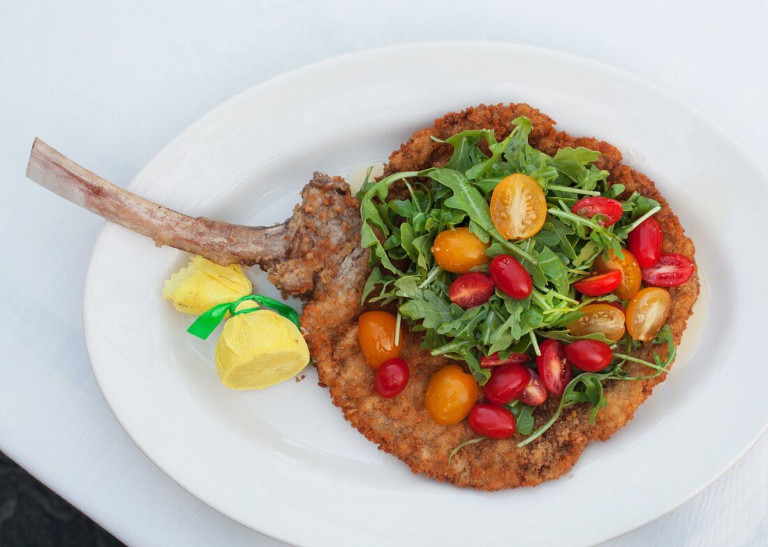 A breaded lamb chop with rocket and cocktail tomatoes