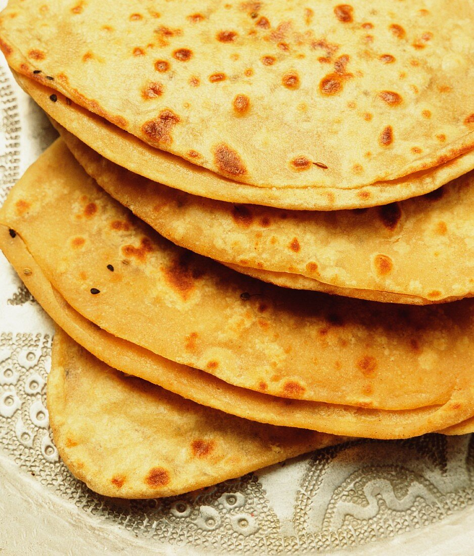 A stack of freshly baked naan bread