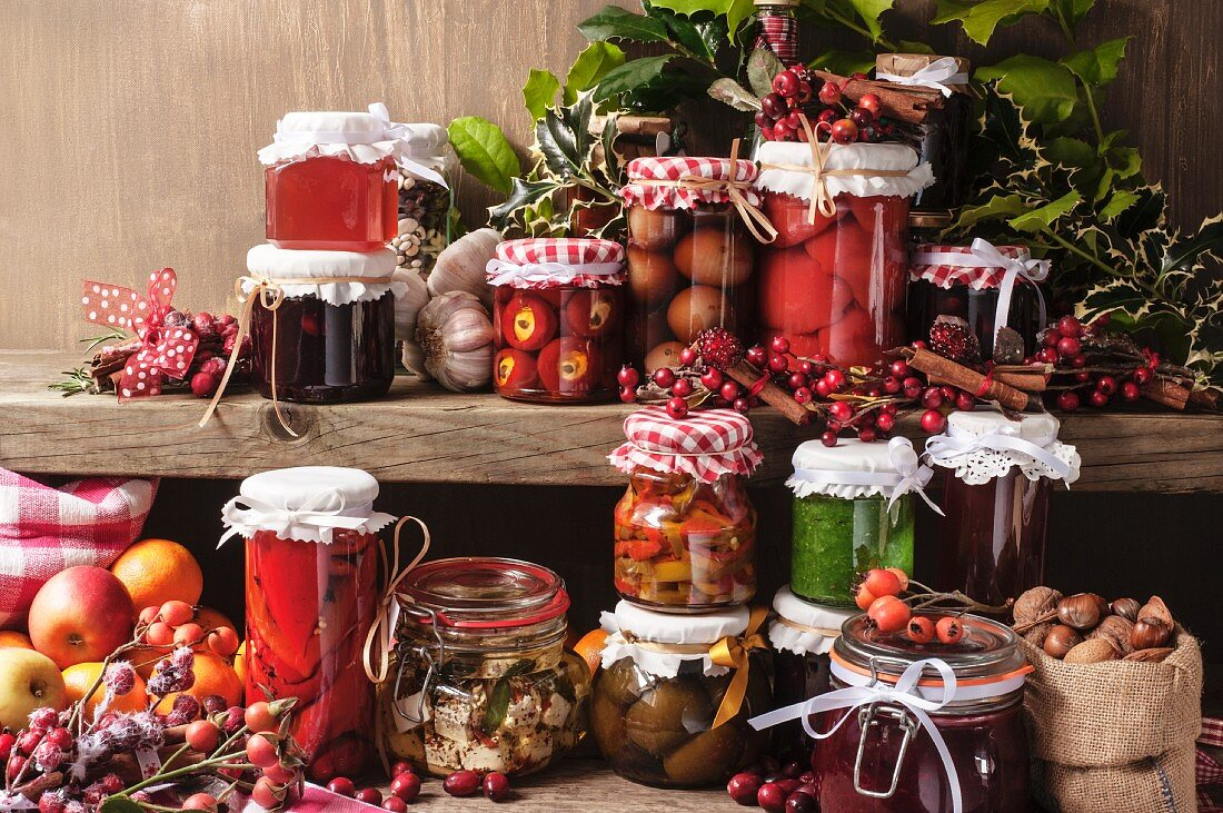 Jars of pickled peppers, onions, preserved figs, pesto and medlar jelly on a wall shelf for Christmas
