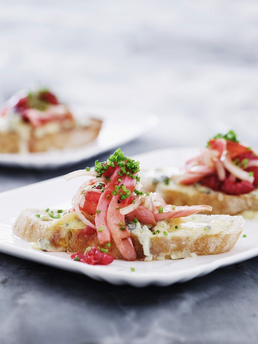 A slice of bread topped with cheese and a marinated asparagus and raspberry salad