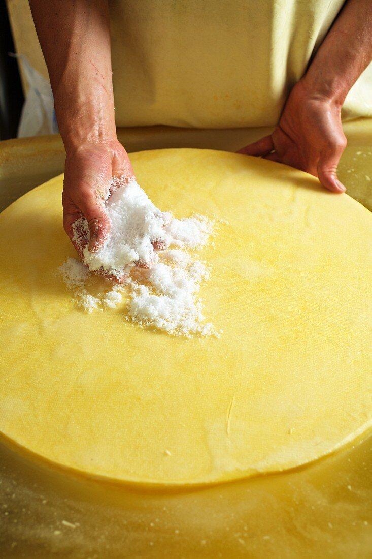 Käselaib wird mit Salz eingerieben (Bregenzerwald, Vorarlberg, Österreich)