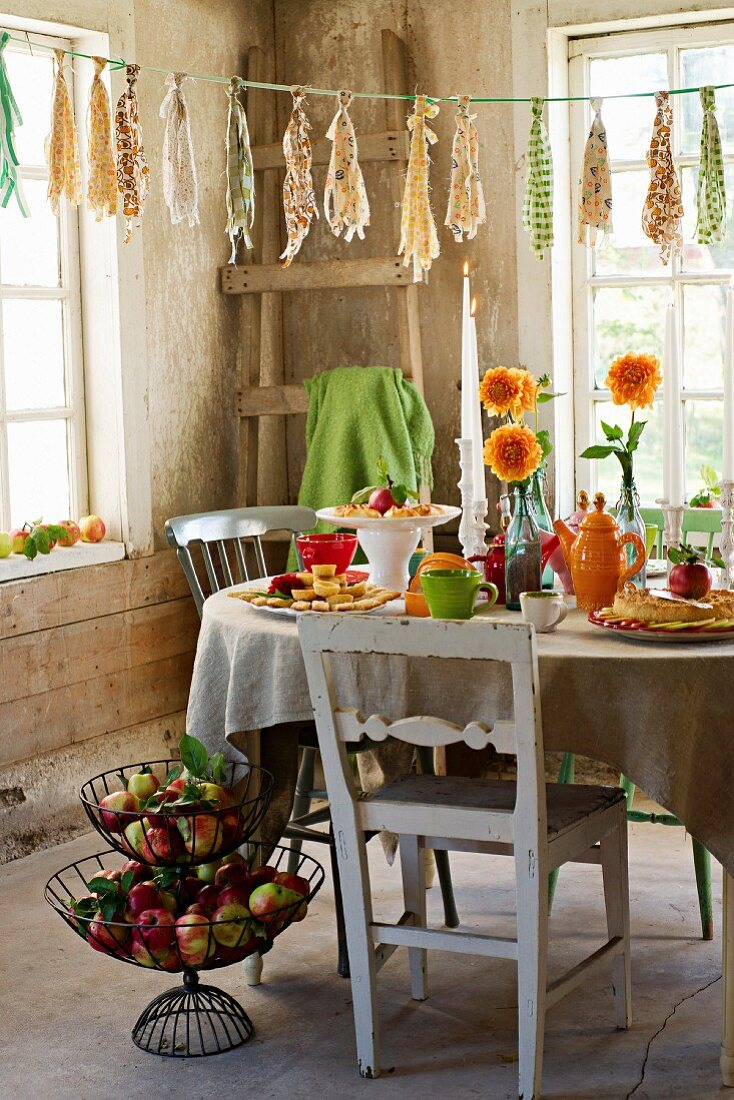 A table laid with apple chips, apple pastries, a vase of flowers and tea crockery