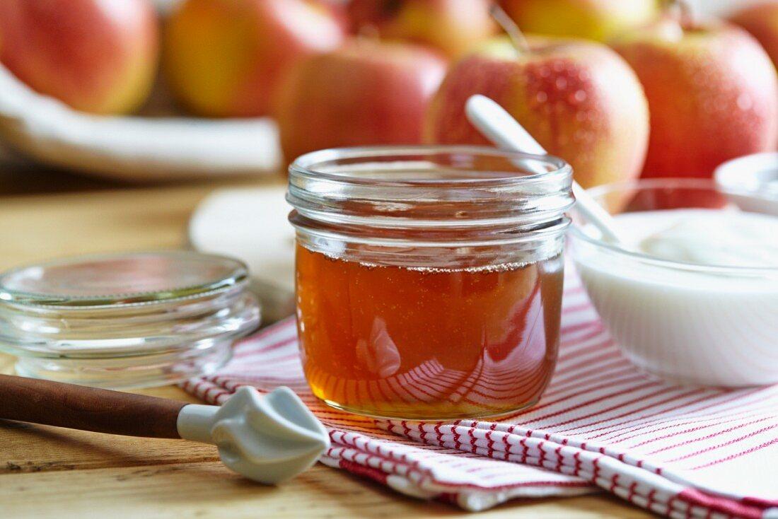 A jar of honey, yogurt and fresh apples