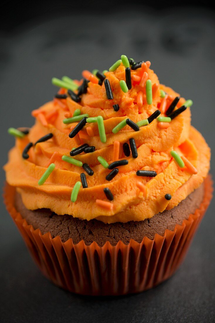 A chocolate cupcake with orange buttercream and sugar sprinkles for Halloween