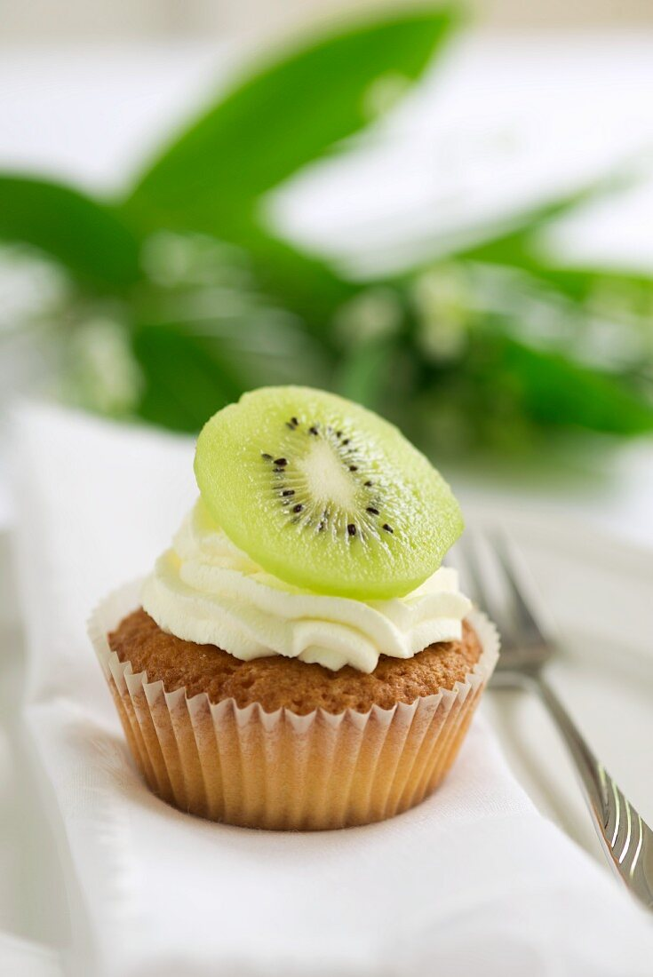 A cupcake topped with cream and a slice of kiwi