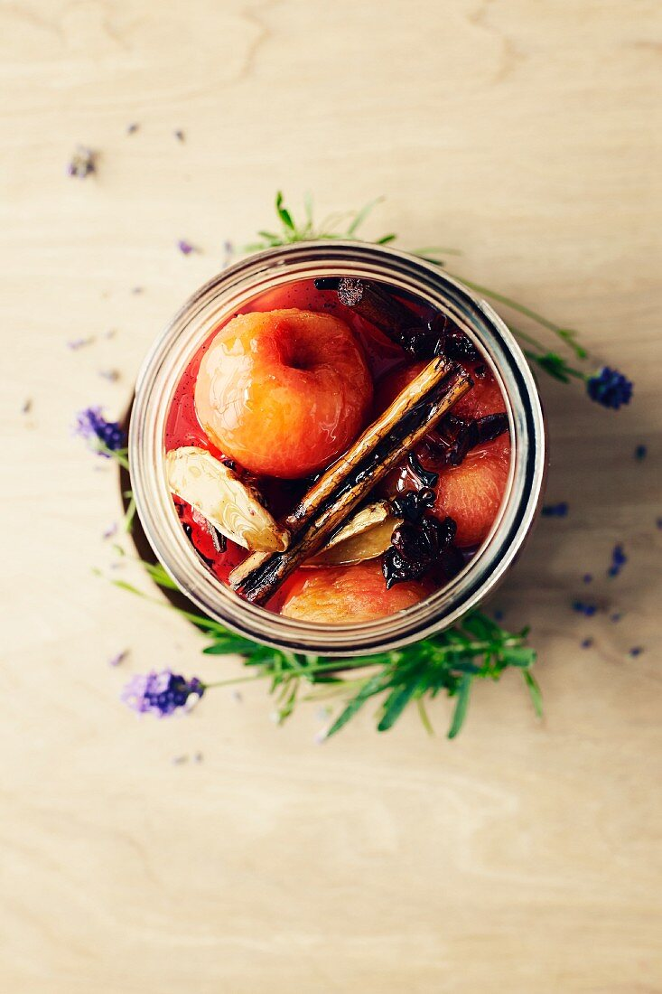 Marinated plums with anise, cinnamon, vanilla and rum in a preserving jar (seen from above)