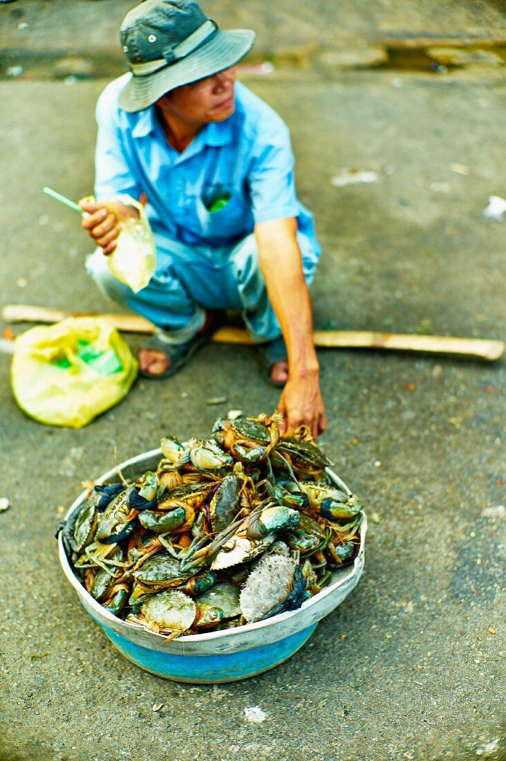 A man selling crustaceans at a market in Saigon (Vietnam)