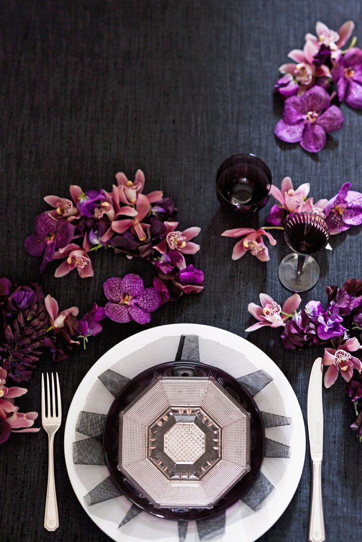 A backdrop for decadent dining (a place setting, purple orchids and glasses)