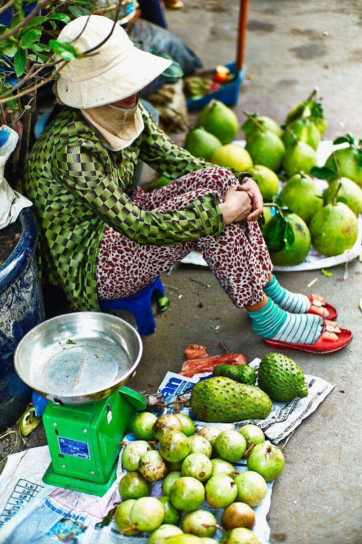 A woman selling fruit at a market in Saigon (Vietnam)