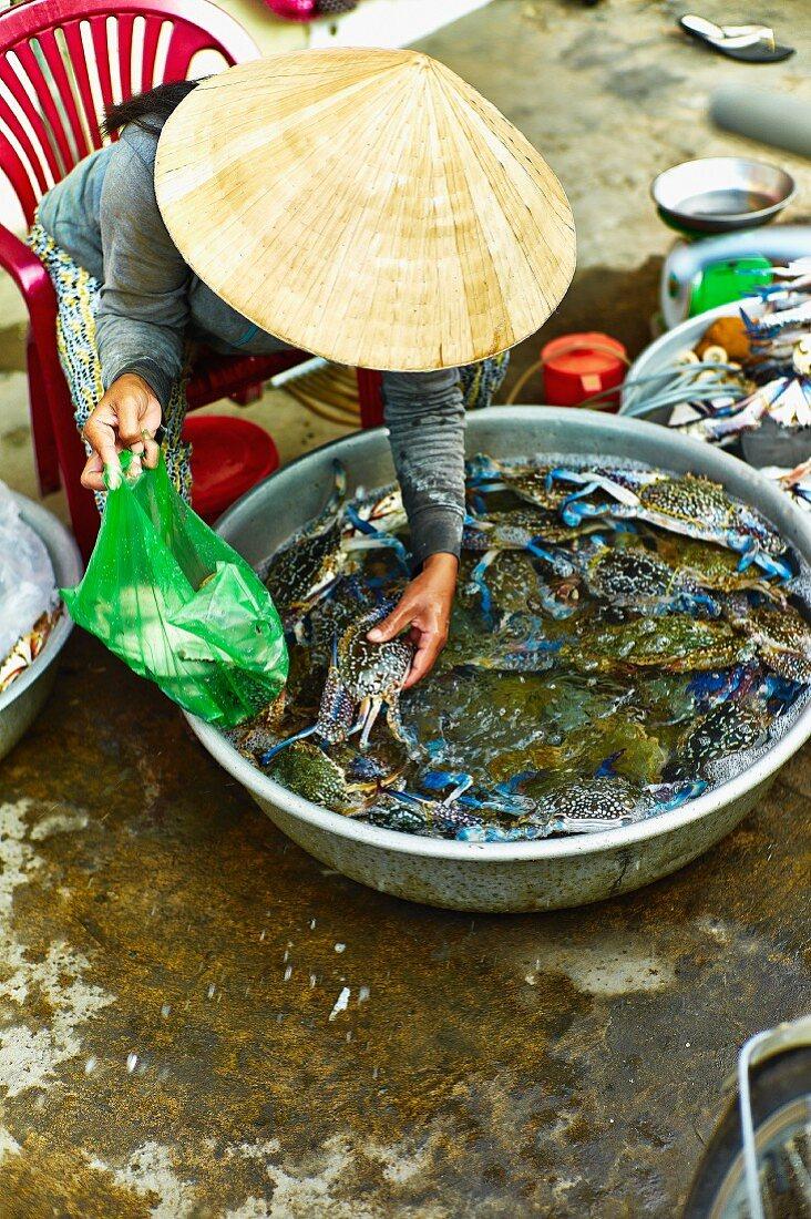 A woman selling fresh blue crabs at a market in Saigon (Vietnam)