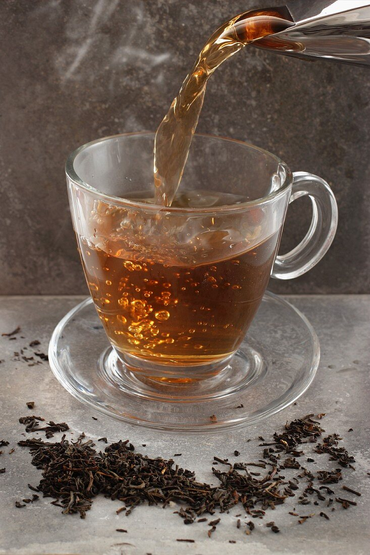 Tea being poured into a glass cup