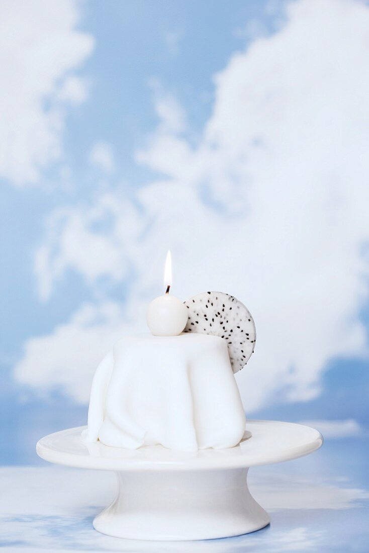 Orange and lemon cake with icing sugar and a candle