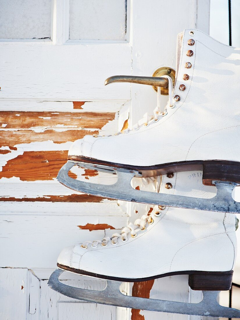 Ice skates hanging from shed door