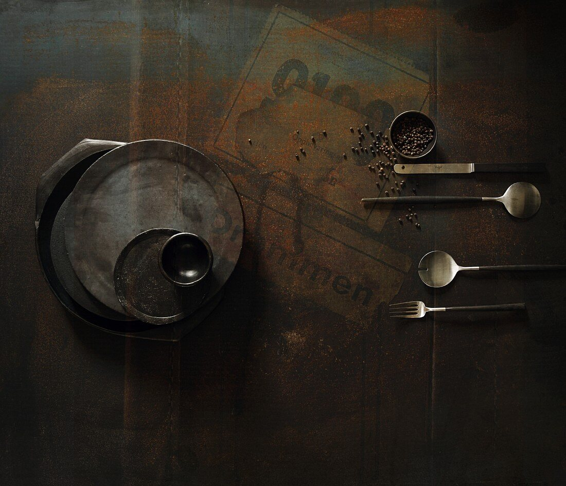 Rustic crockery and cutlery on a dark surface