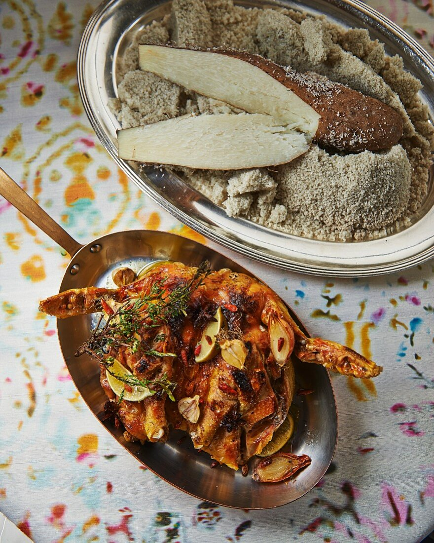 Antilles-style spicy chicken next to a bowl of cassava flour and cassava roots