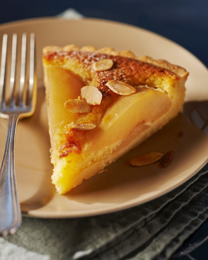 A slice of pear tart with slivered almonds