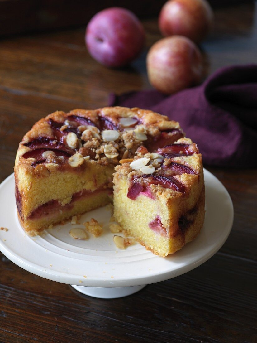 Sliced, gluten free plum cake with almonds and crumbles on a round cake plate