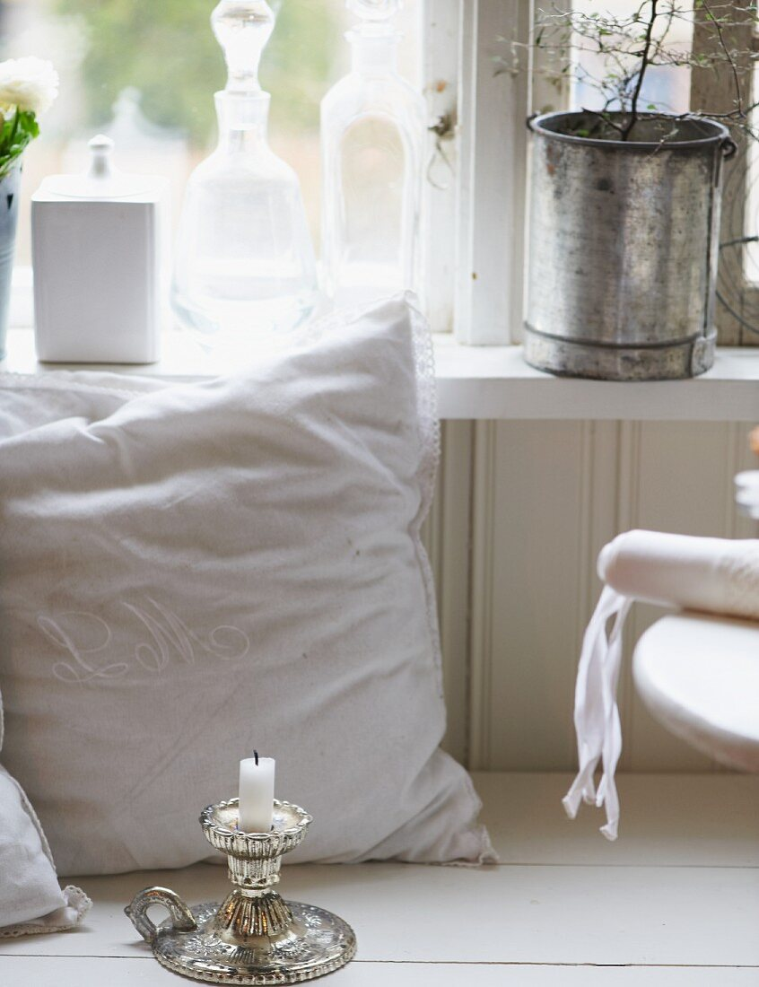 Cushion, candlestick, bottles and potted plants in front of window