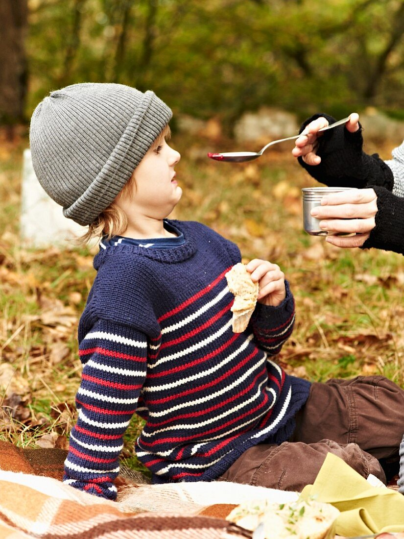 A woman feeding a child beetroot soup at an autumnal picnic