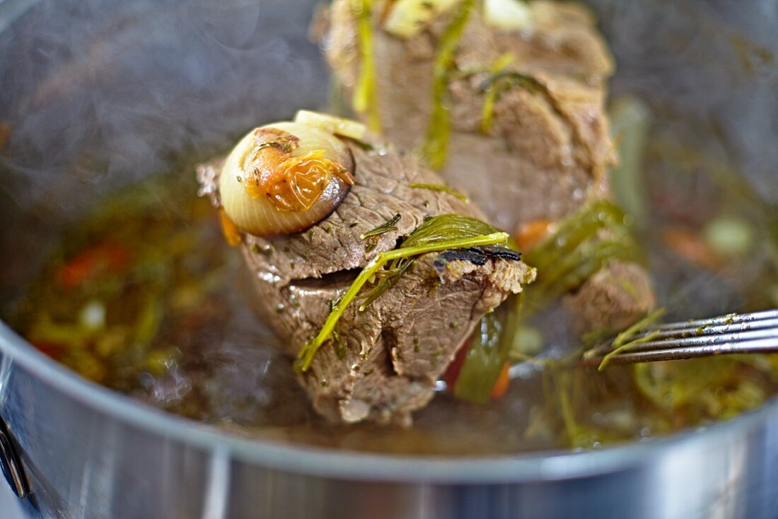 Soup meat on a ladle over a pot