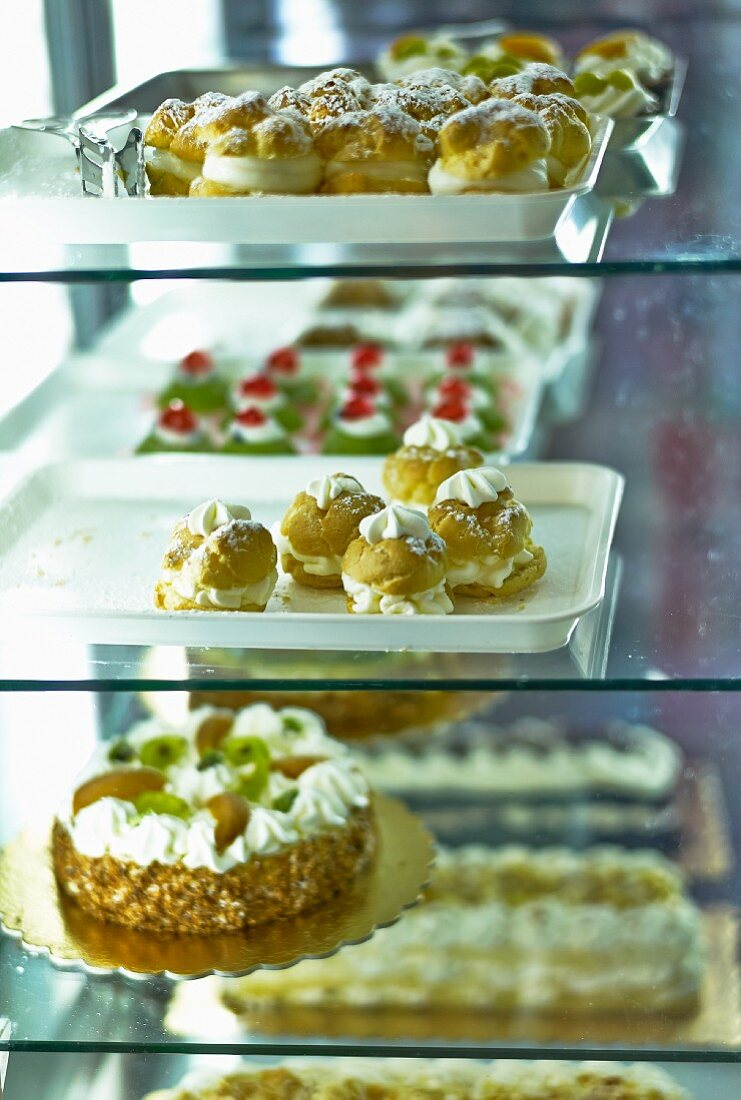 Various cakes and pastries in a refrigerated display cabinet