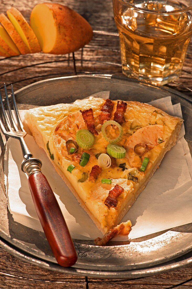 A slice of spicy potato cake with apple wedges, onions and bacon