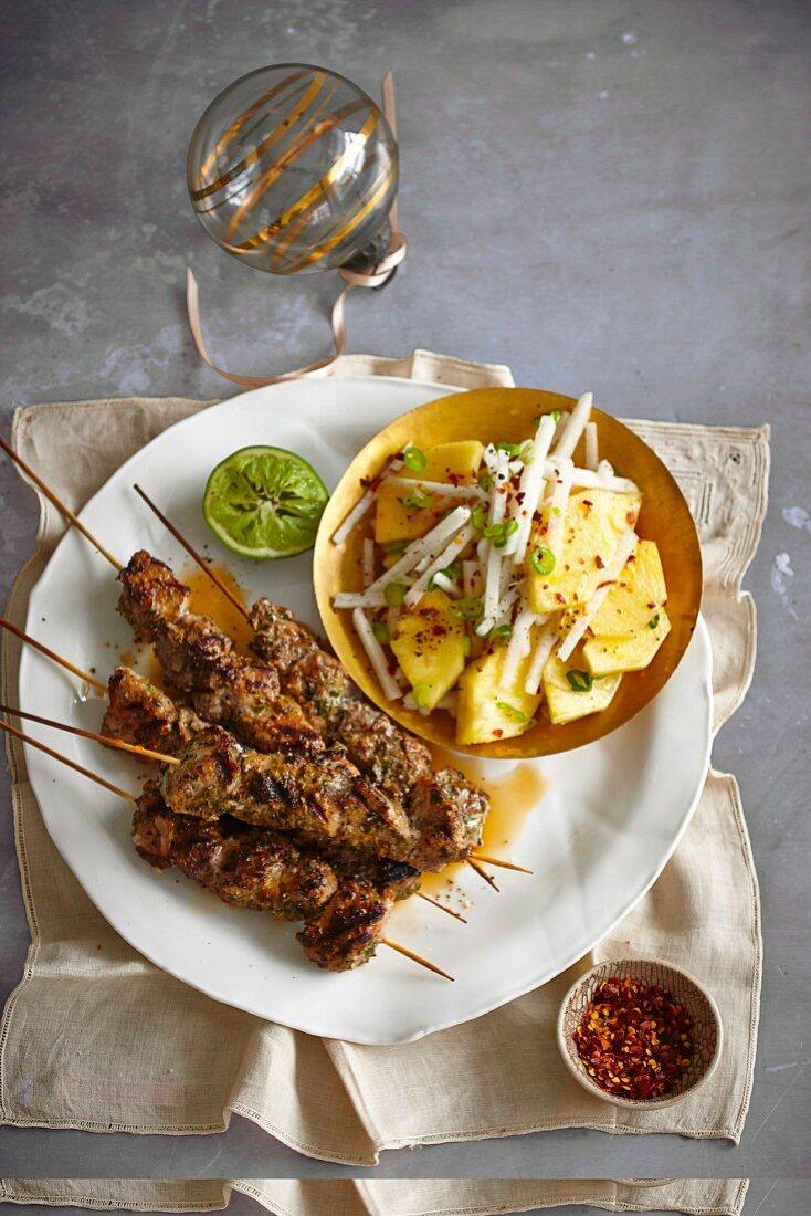 Marinated pork skewers with a pineapple and jicama salad