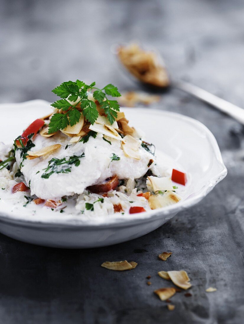 Cod on a bed of rice with peppers and coconut sauce