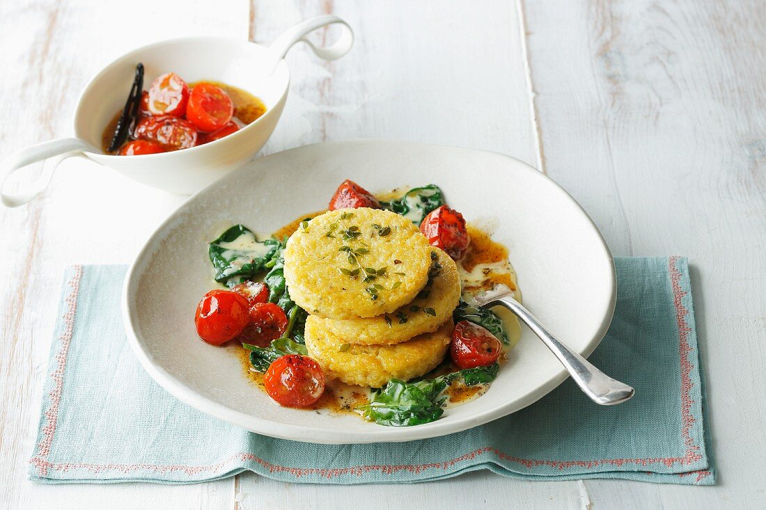 Millet cakes on a bed of tomatoes, spinach and orange sauce
