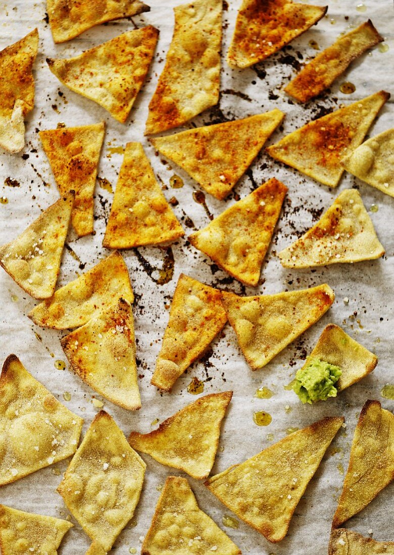 Homemade tortilla chips on baking paper, one topped with guacamole