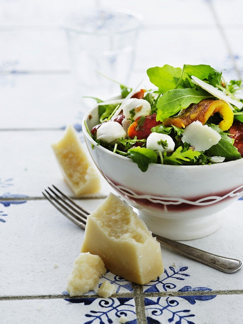 A mixed leaf salad with grilled pepper strips, mozzarella and Parmesan cheese