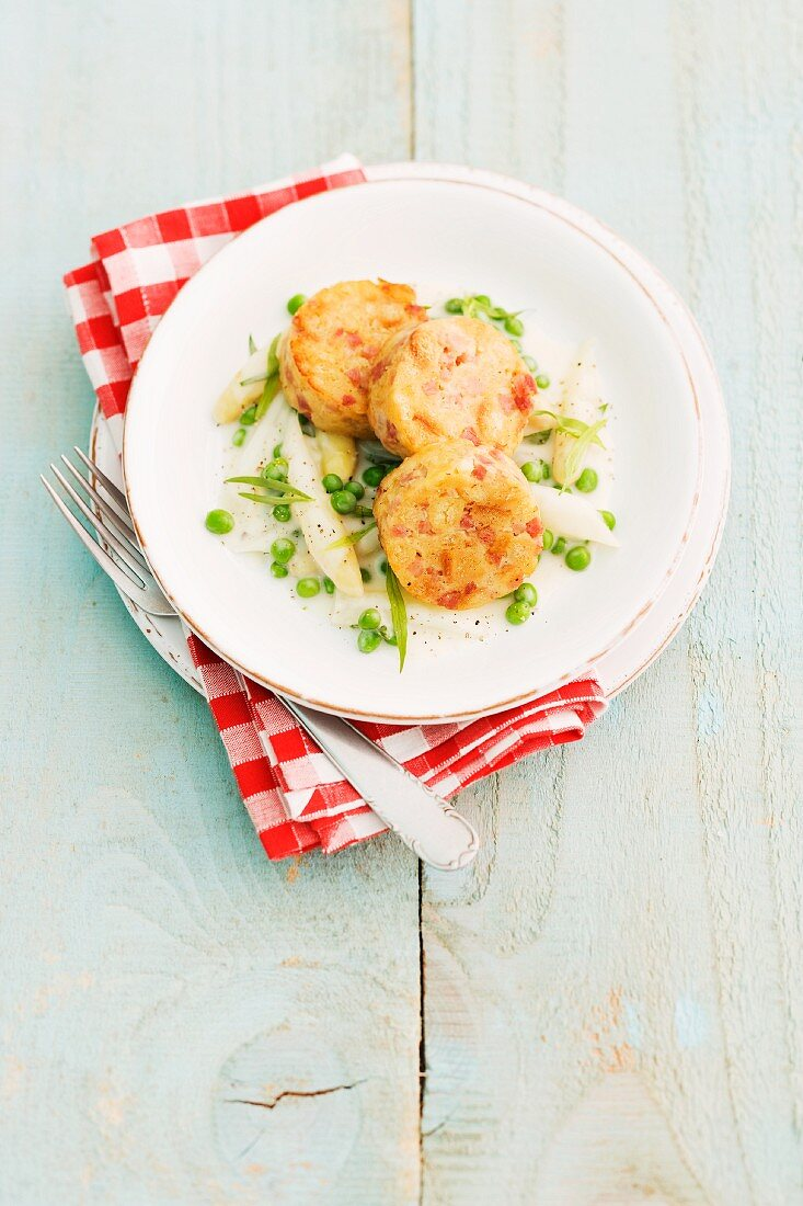Bread dumplings with ham on a pea and asparagus medley