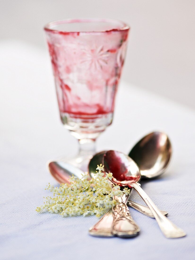 An empty dessert glass that once contained elderflower jelly