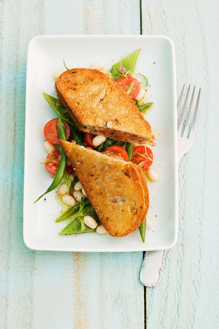 Ciabatta with lamb on a bean and tomato salad