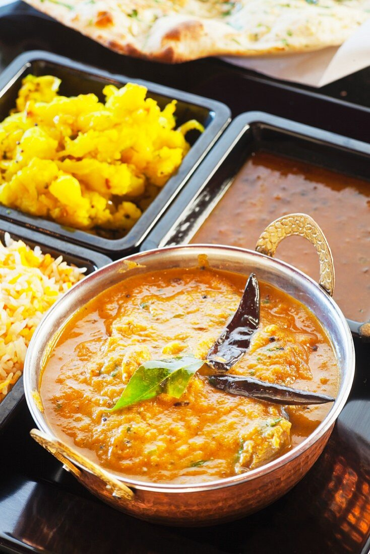 Chicken Chettinad with curried potatoes, rice, and lentils (India)