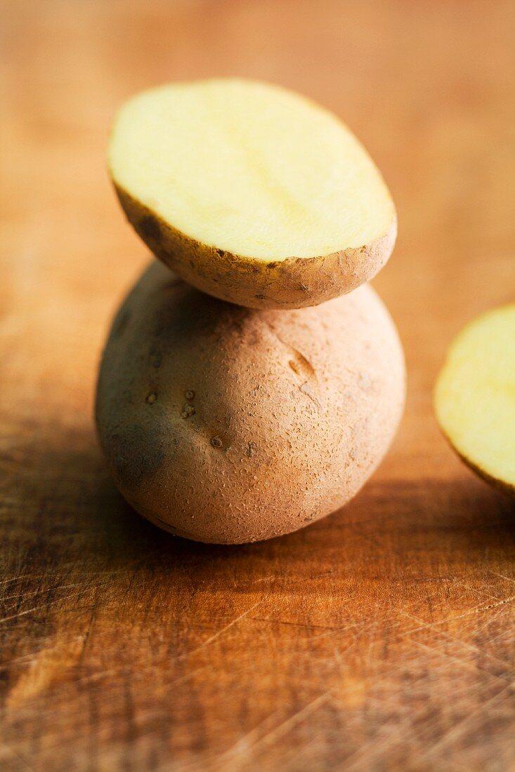 Agria-Kartoffeln, ganz und halbiert, auf Holzuntergrund