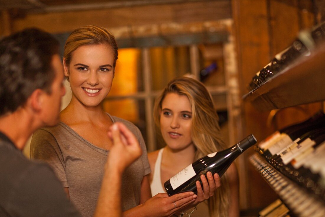 Young women receiving expert advice while buying wine