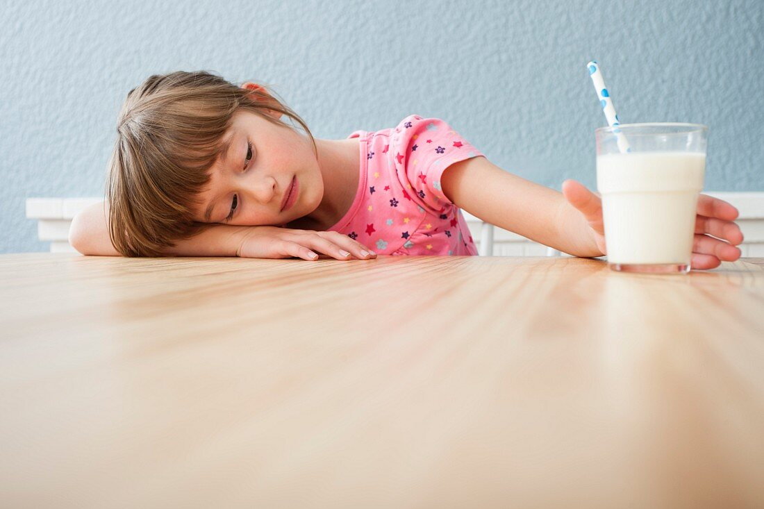 A tired girl with a glass of milk