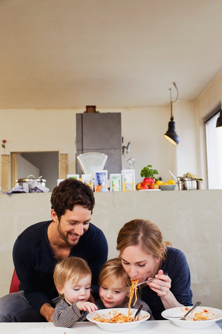 A young family eating spaghetti