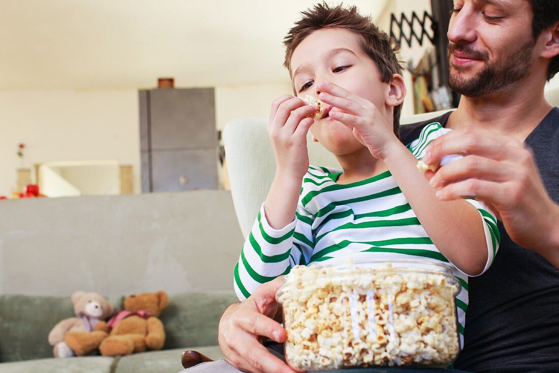 A boy eating popcorn while sitting on his father's lap