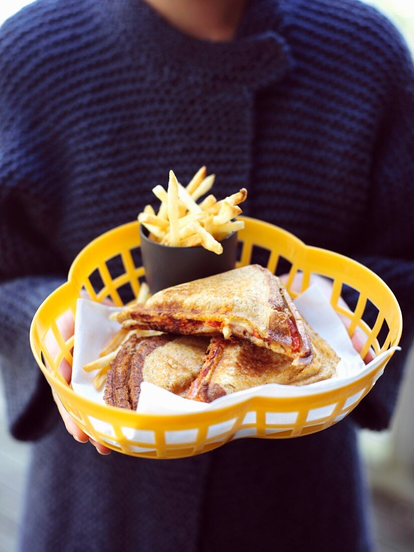 A woman holding a toasted cheese sandwich and fries in a plastic basket