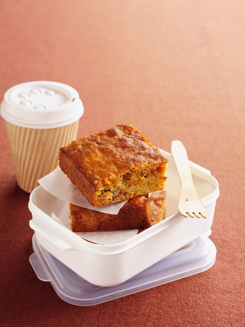Carrot cake in a lunch box next to a cup of coffee