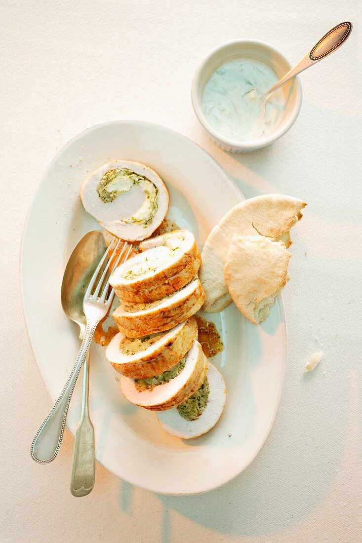 Sliced turkey roulade filled with white cabbage and sheep's cheese served with pita bread