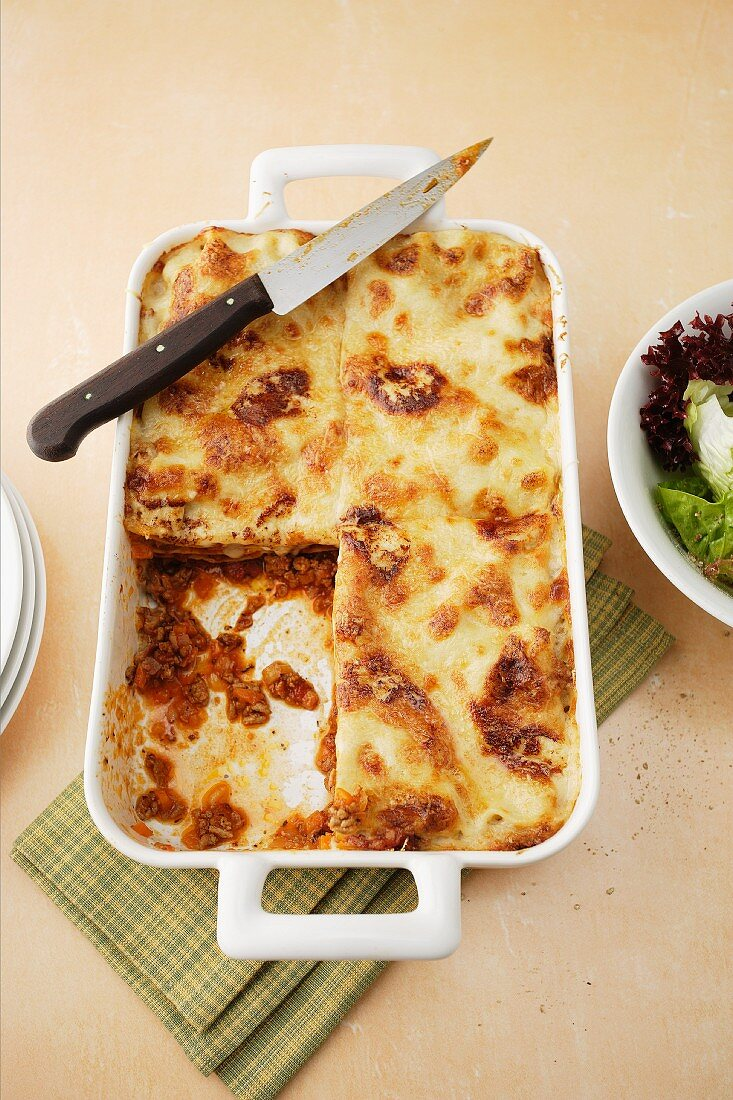 Lasagne in a baking dish with a slice cut out