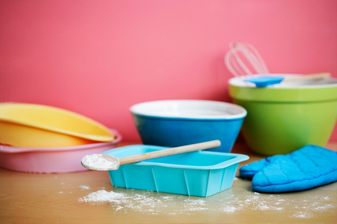 Various baking dishes, flour, a wooden spoon and an oven glove