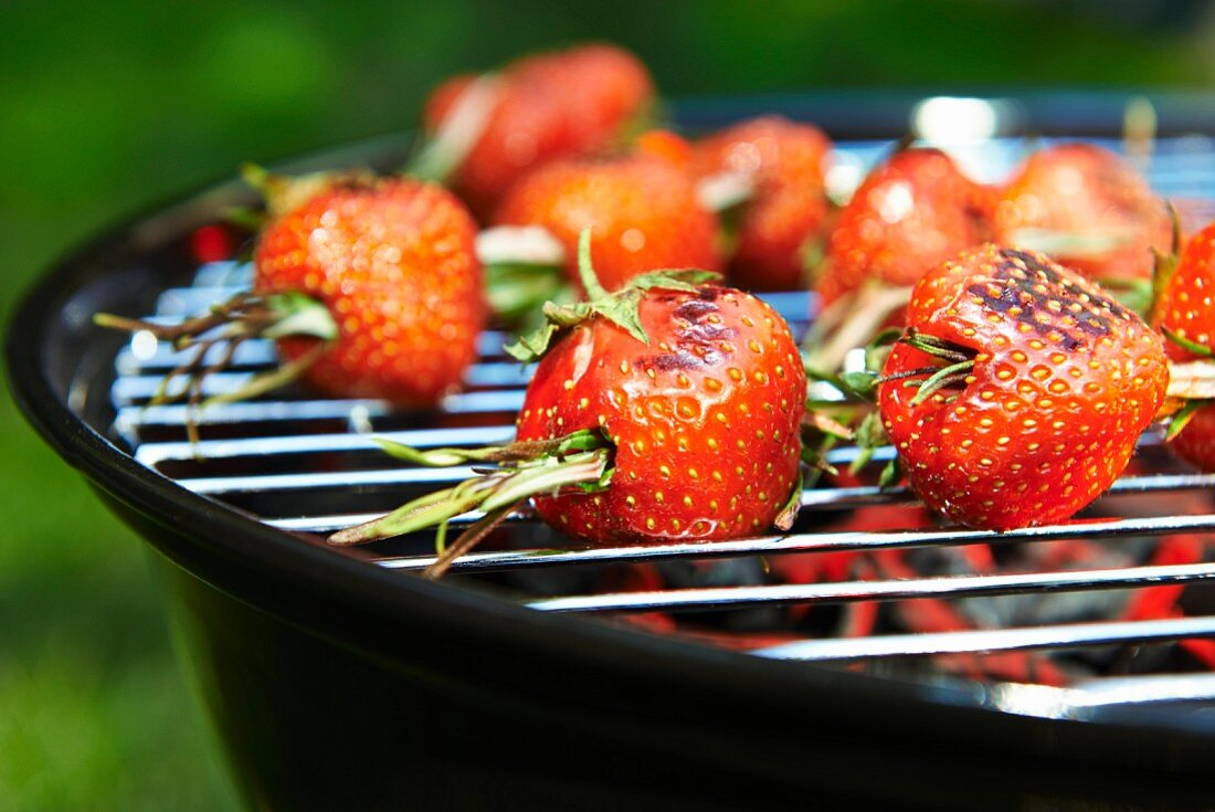 Strawberries with rosemary on a barbecue