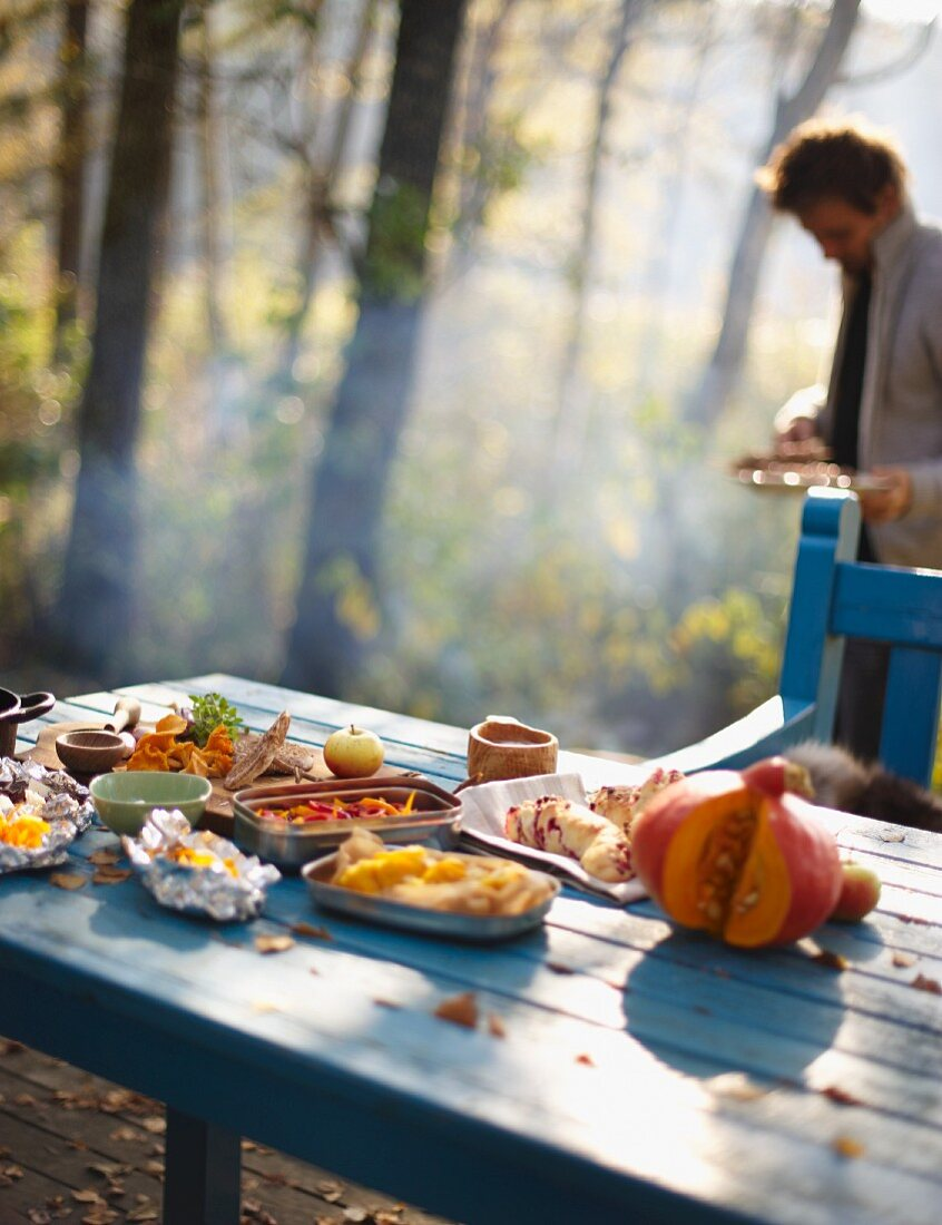 An autumnal picnic set out on a wooden table in a forest